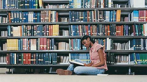 Student in library reading a book
